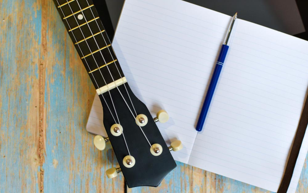 ukulele-fretboard-notepad-wooden-table-independent-online-learning-play-hawaiian-guitar